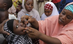 A health worker administers a polio vaccine to a child in Kawo Kano, Nigeria.
