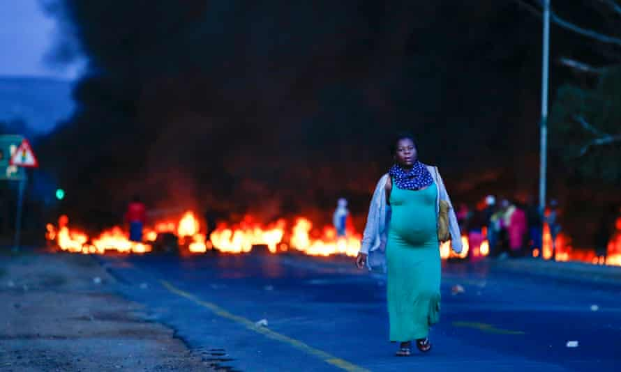 A heavily pregnant lady walks away from a burning barricade across Kommetjie Road during a protest against the lack of policing in Cape Town.
