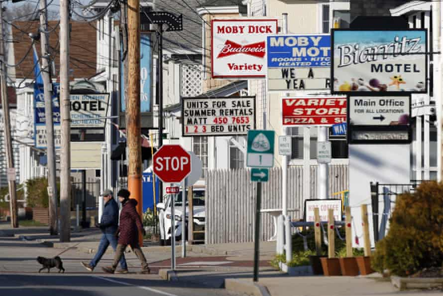 A couple walks by a row of motels closed by the coronavirus pandemic in Old Orchard Beach, Maine.
