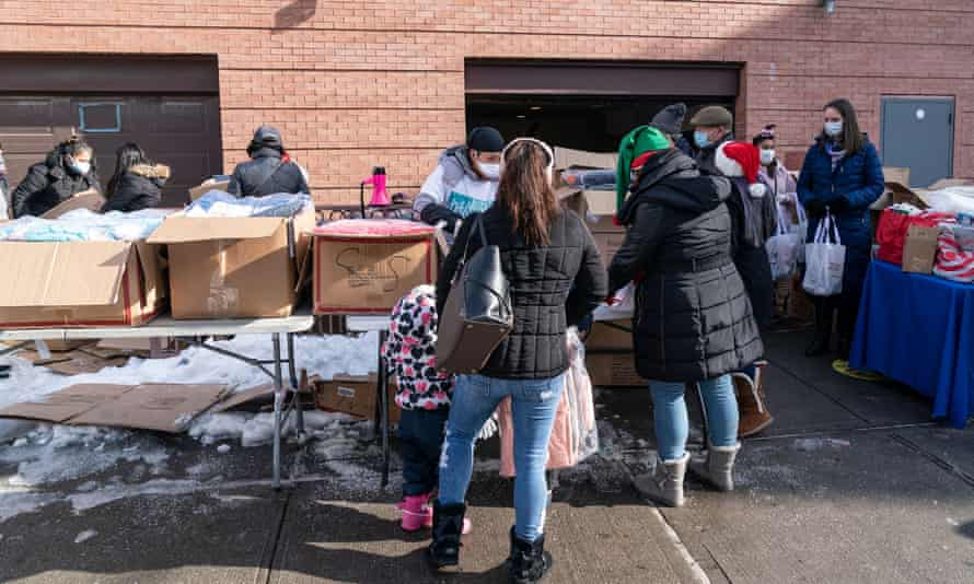 Volunteers distribute holidays toys and winter coats in Corona, Queens, New York, to a line of people stretching seven blocks. Many people lost their jobs and rely on free food and clothing distribution.