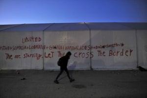 A volunteer walks past a tent