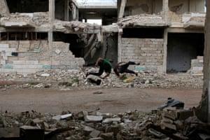 Parkour coach Ibrahim al-Kadiri (L), 19, and Muhannad al-Kadiri, 18, demonstrate their Parkour skills in the rebel-held city of Inkhil