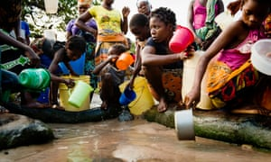 Women and children gather to collect water from a water source in Mossuril district in Mozambique. Almost half of the country's 26 million population don't have access to safe water