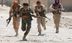 Kurdish fighters run across a street in Raqqa, Syria on July 3, 2017