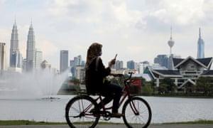 A woman rides a bicycle at a park, amid the coronavirus pandemic, in Kuala Lumpur, Malaysia.