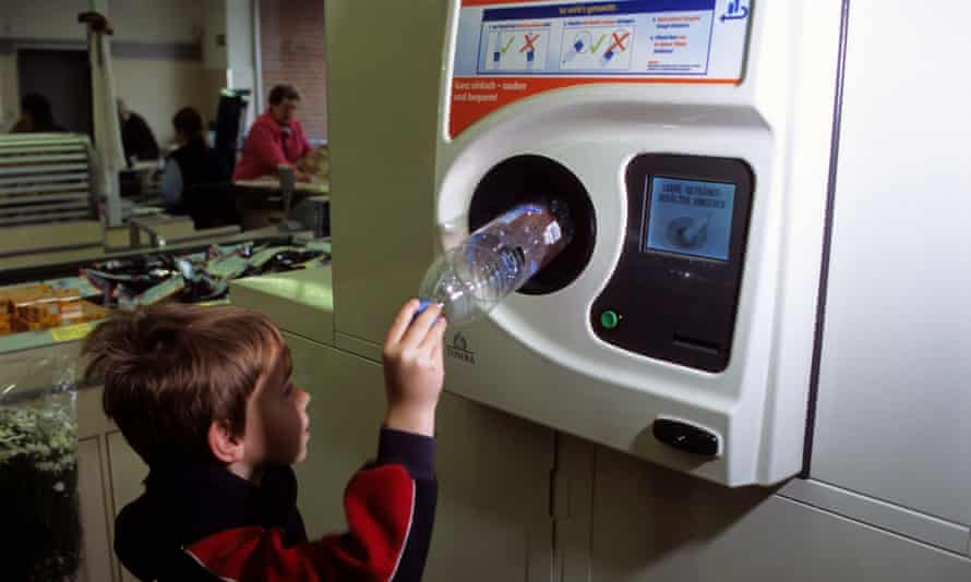 A young boy recycles plastic bottles in an automatic bottle bank inside a supermarket, Leichlingen, Germany