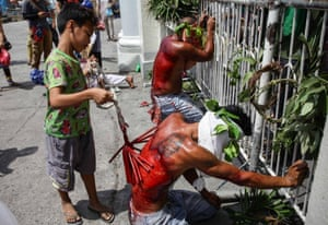 A boy whips a flagellant on Maundy Thursday in San Fernando, Philippines