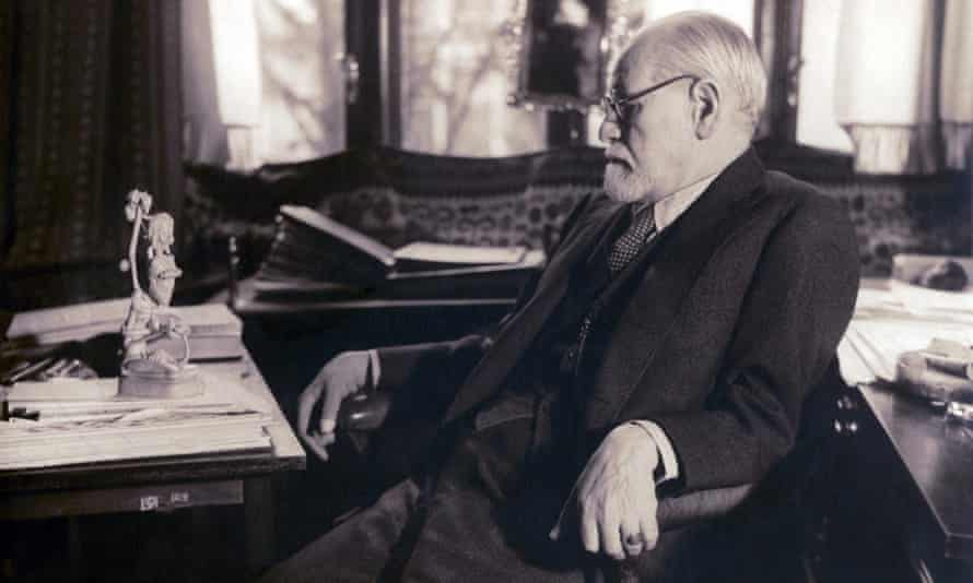 Sigmund Freud at his desk, contemplating a carved figurine, 1937.