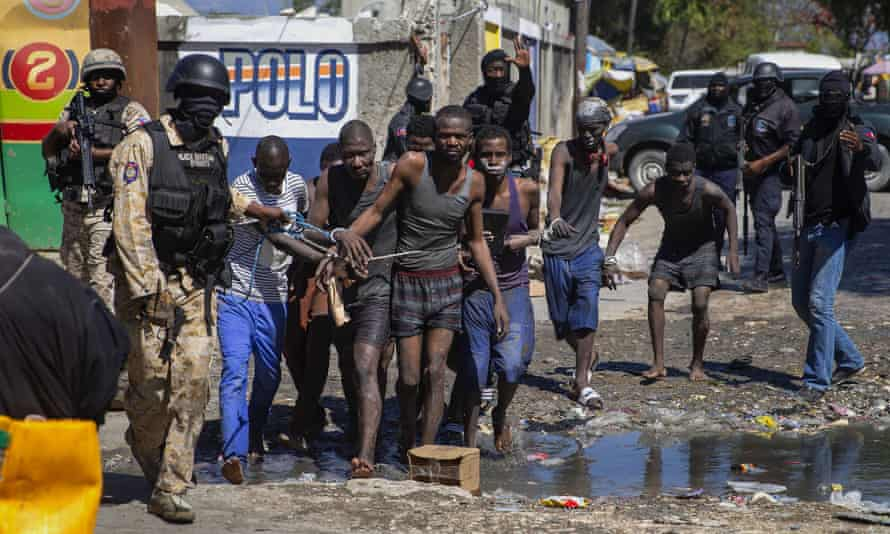 Recaptured inmates are led by police outside the Croix-des-Bouquets Civil Prison after a breakout, in Port-au-Prince, Haiti on 25 February 2021
