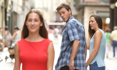 Man walking with girlfriend and looking over shoulder at another woman