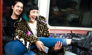 Two young stylish women laughing on underground train carriage