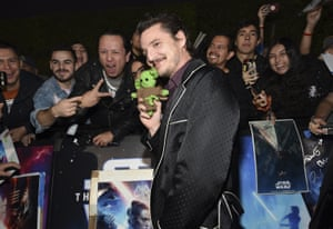 Pedro Pascal holds a baby Yoda doll as he poses with fans.
