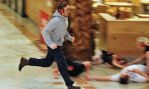 An actor playing the part of a shopper, runs for cover during the simulation at the Trafford centre.