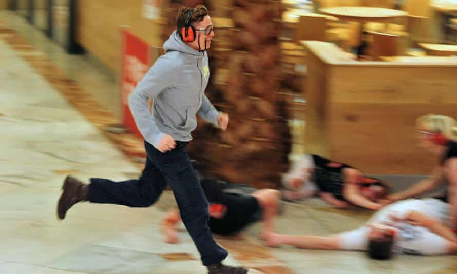 An actor playing the part of a shopper runs for cover.