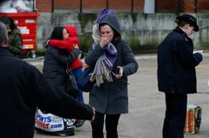 A woman reacts as police officers interview people near to the scene where a man was shot and killed by armed police.
