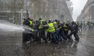 Gilets jaunes protesters feel the force of a water cannon on the Champs-Élysées in Paris