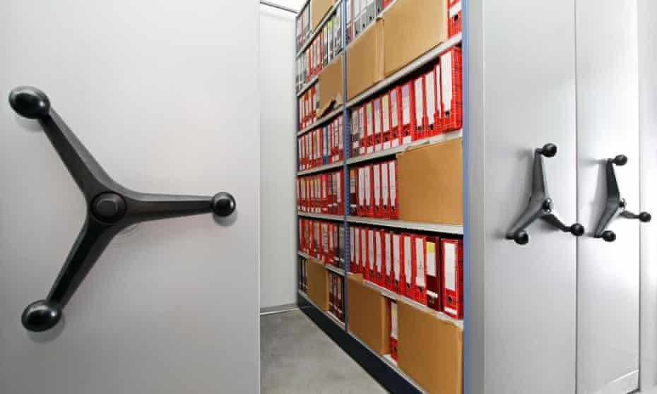 Sliding shelves with folders of documents.