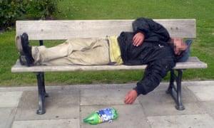 A man drunk on cheap cider on a park bench