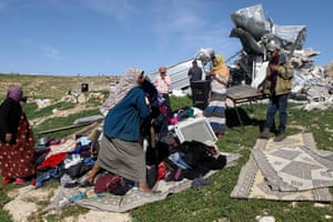 Palestinians collect their belongings after Israeli forces demolished their house in Yatta, West Bank