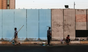 Workers paint blast walls, ubiquitous in Baghdad since the American invasion in 2003. Authorities say they will now begin building a wall and trench to encircle the city.