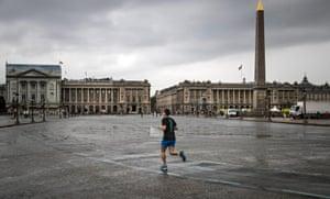 A man jogs across Place de la Concorde
