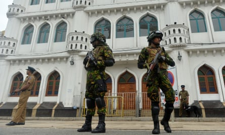 Security personnel stand guard outside a mosque during Friday prayers in Colombo