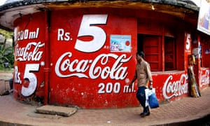 (FILES) In this picture taken 03 December 2003, An Indian man walks past the bottom section of a three storey corner store emblazoned with Coca-Cola signage, advertising 200ml bottles of coke at 5 Indian Rupees (US 10 cents) in a street in Goa. A court in southern India lifted a ban 22 September 2006, on the manufacture and sale of soft drinks by US giants Coca-Cola and Pepsi. The communist government in Kerala state imposed the ban on August 11 after claims by a New Delhi-based environmental group that the products contained high levels of pesticides. AFP PHOTO/Rob ELLIOTT/FILES (Photo credit should read ROB ELLIOTT/AFP/Getty Images)