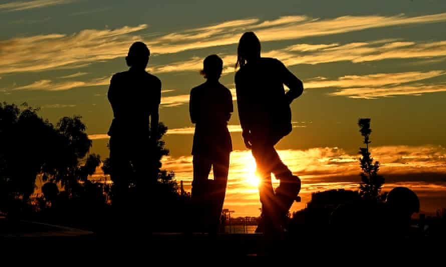 Silhouettes of boys at a skate park.