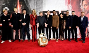 A bunch of people standing on a red carpet. And a small robot