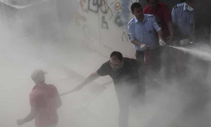 A policeman in plain clothes hits a migrant, as another sprays a fire extinguisher.