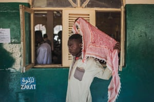 A man covers his head before Friday prayers in Pemba