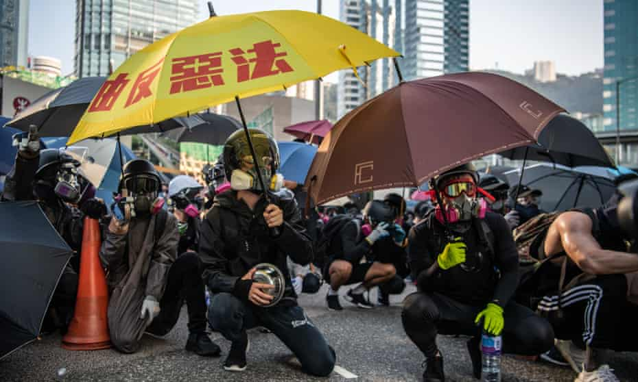 Protesters with umbrellas crouch in the street