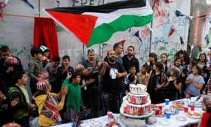 Man holds a Palestinian flag as people take part in an event ahead of the anniversary of the Balfour Declaration, outside Banksy's Walled Off Hotel in the West Bank city of Bethlehem