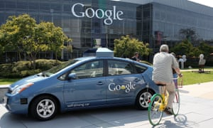A bicyclist rides by a self-driving car being developed at the Google headquarters in California in 2012.