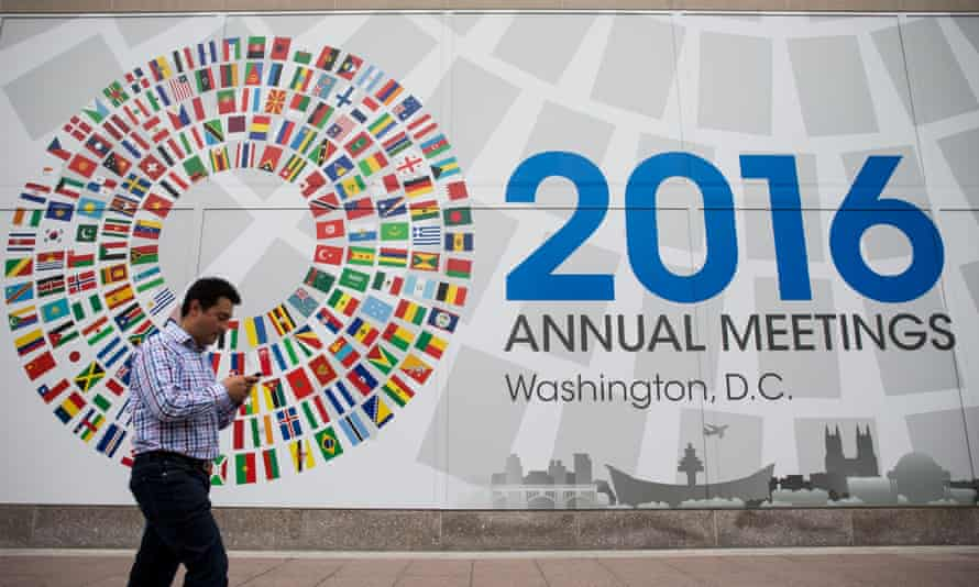 a man passes the 2016 Annual Meetings sign at the IMF offices