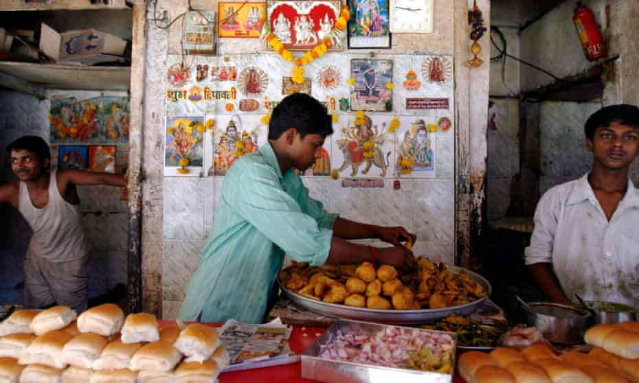 A street stall selling vada pav, a spicy fried potato ball served in a bun.