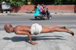 A man practices yoga on a pavement in Amritsar, India