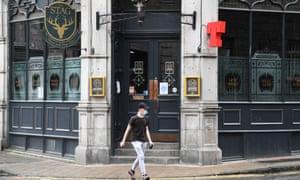 A pedestrian walks past a closed pub in Aberdeen