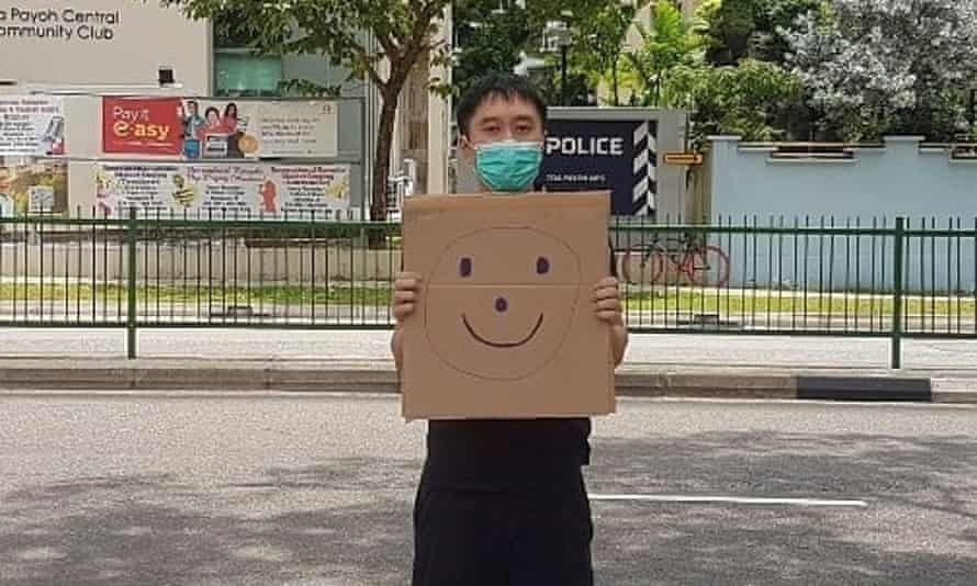 Jolovan Wham wears a mask and holds a cardboard with a drawing of a smiley face outside a Singapore police station in March.
