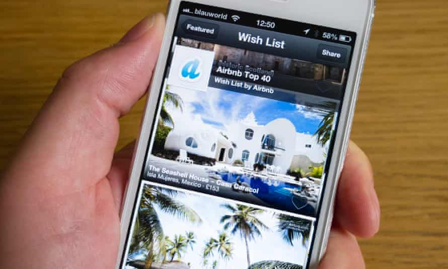 Someone uses the Airbnb app to look at holiday accommodation on an iPhone