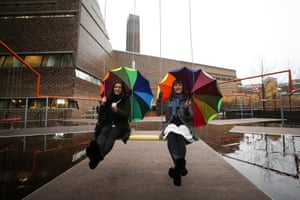 London, UK. Two women pose for pictures as part of the One Two Three Swing! art installation by the Danish collective Superflex at the Tate Modern gallery