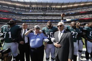 Philadelphia Eagles players and owners Jeffrey Lurie stand for the national anthem - the Eagles' Malcolm Jenkins raises his fist next to Lurie.