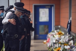 Croydon, EnglandA police officer comforts a colleague while paying tribute to Sgt Matiu Ratana outside Croydon custody centre. Ratana, 54, was shot dead in the early hours of Friday 25 September at Croydon custody suite. A handcuffed man being checked in by Sgt Ratana opened fire before turning the weapon on himself