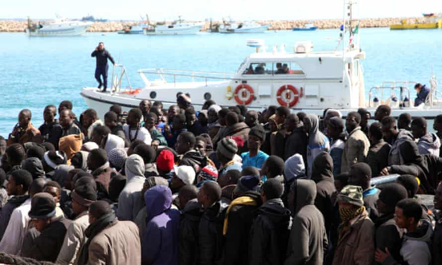 Migrants wait to disembark from a tug boat after being rescued in the Mediterranean. An Italian government official says four smugglers brandishing Kalashnikovs threatened an Italian Coast Guard motorboat that had just rescued migrants off the coast of Libya.