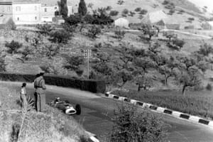 Spectators look on as Luigi Musso drives his Ferrari 801 in the hills above Pescara.