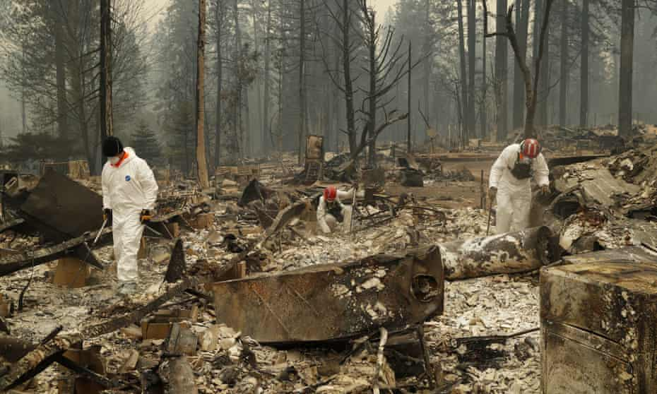 Search and rescue workers search for human remains at a trailer park burned by the Camp fire in Paradise.