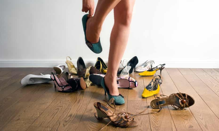 Woman's legs surrounded by shoes.