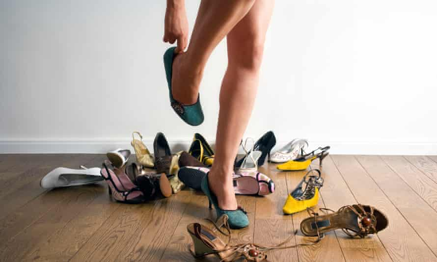Woman's legs surrounded by shoes