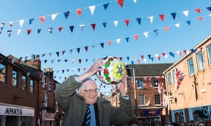 Bill Millward, then aged 100, holds the ball aloft during the 2016 Royal Shrovetide football match.