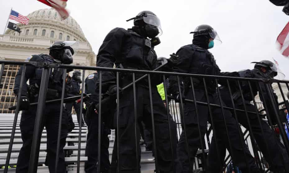 Law enforcement position themselves as a pro-Trump mob gathers outside the US Capitol building on 6 January 2021.